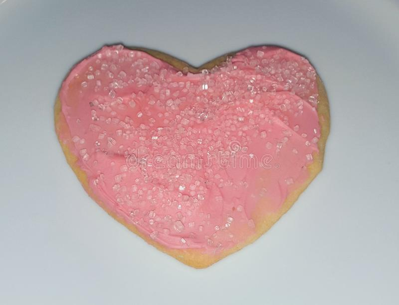 A heart shaped sugar cookie with pink icing and pink sprinkles for Valentine& x27;s Day royalty free stock image