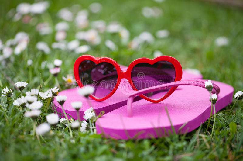 Heart shaped sunglasses and flip flops in the grass. Heart shaped sunglasses and pink flip flops in the grass royalty free stock image