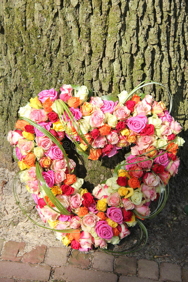 Heart shaped sympathy flowers. Heart shaped sympathy arrangement, roses in various bright colors royalty free stock photography