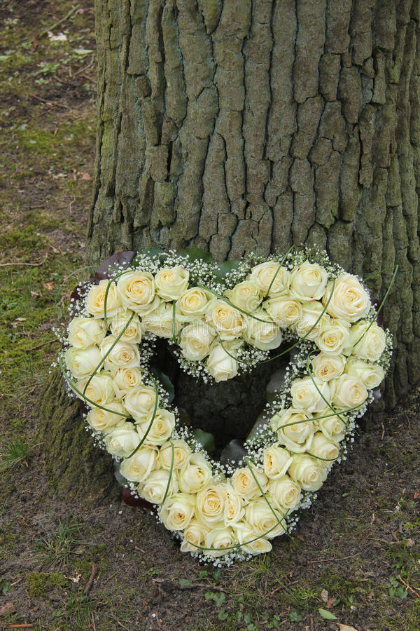 Heart shaped sympathy flowers. Heart shaped sympathy arrangement, white roses and gypsophila royalty free stock images