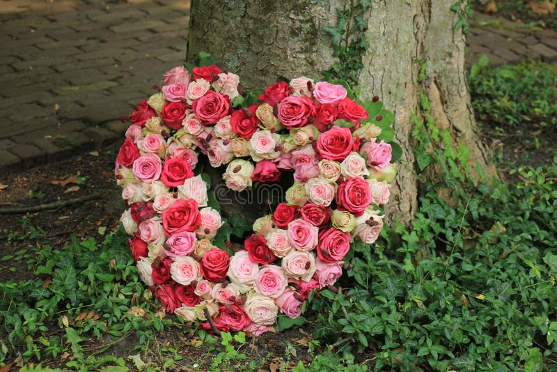 Sympathy flowers near a tree. Heart shaped sympathy flowers or funeral flowers near a tree royalty free stock photography