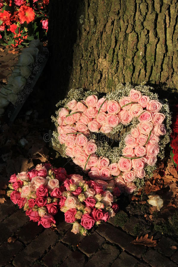 Heart shaped sympathy flowers. Heart shaped sympathy or funeral flowers near a tree stock images