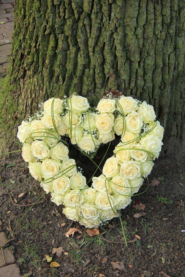 Heart shaped sympathy flowers. Near a tree royalty free stock image