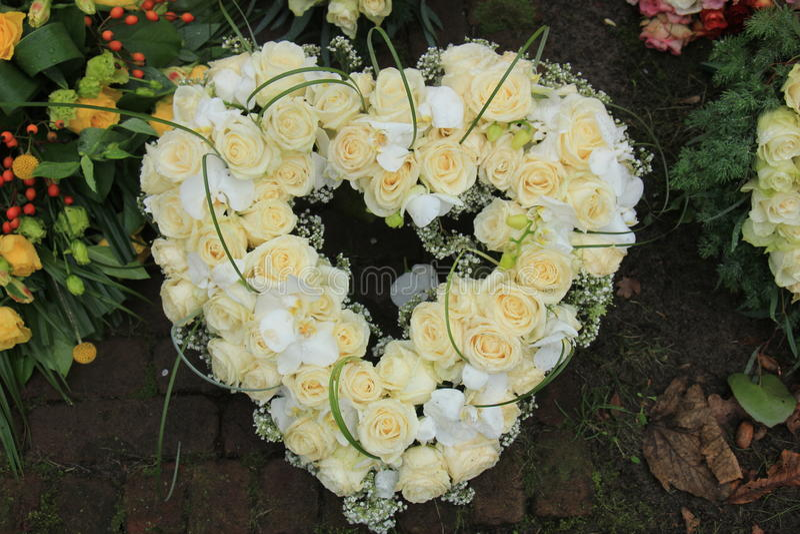 Heart shaped sympathy wreath near a tree. Heart Shaped sympathy or funeral flowers near a tree at a cemetery stock photos