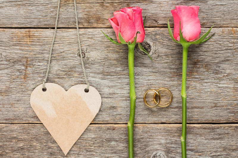 Heart shaped tag,wedding rings and roses stock image
