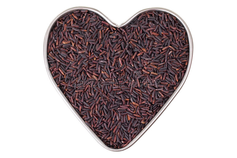 Heart shaped tin pan full of raw Riceberry rice grains in reddish purple isolated on white stock photo