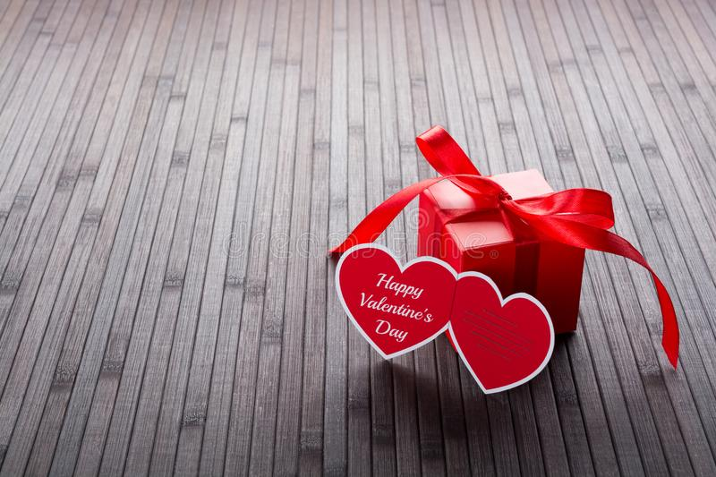 Heart Valentine`s day greeting card and red present box. Heart-shaped Valentine`s day greeting card and red present box stock photography
