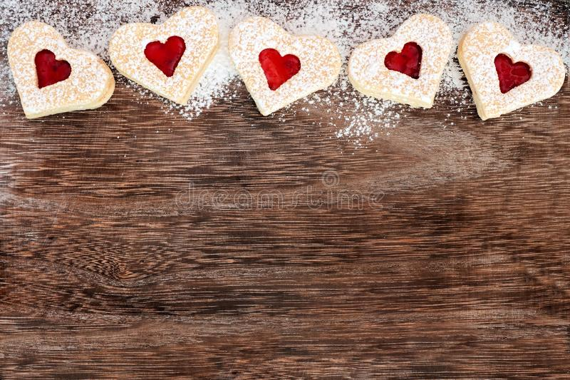 Heart shaped Valentines Day cookies top border over rustic wood. Heart shaped Valentines Day cookies top border with powdered sugar over a rustic wood background royalty free stock photography