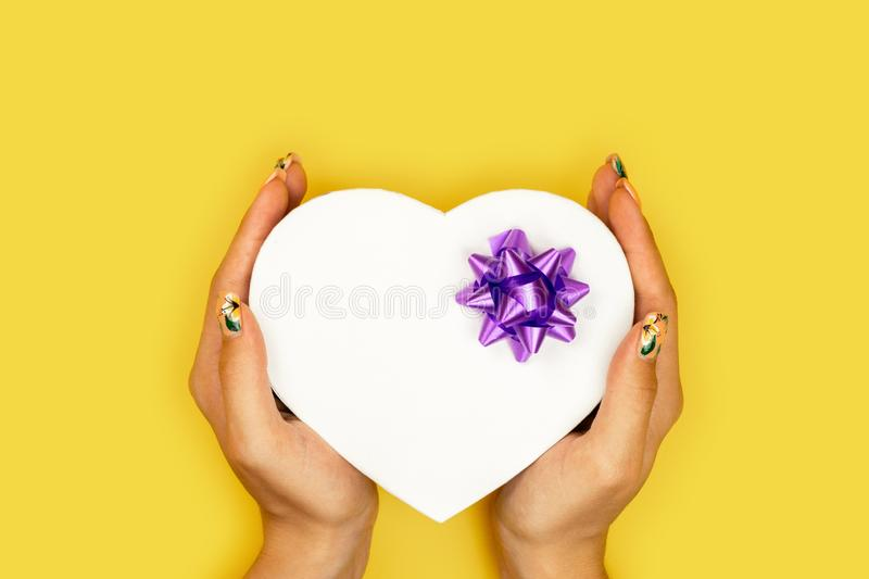 Heart shaped Valentines Day gift box in the hands of the girl on yellow paper background. royalty free stock photos