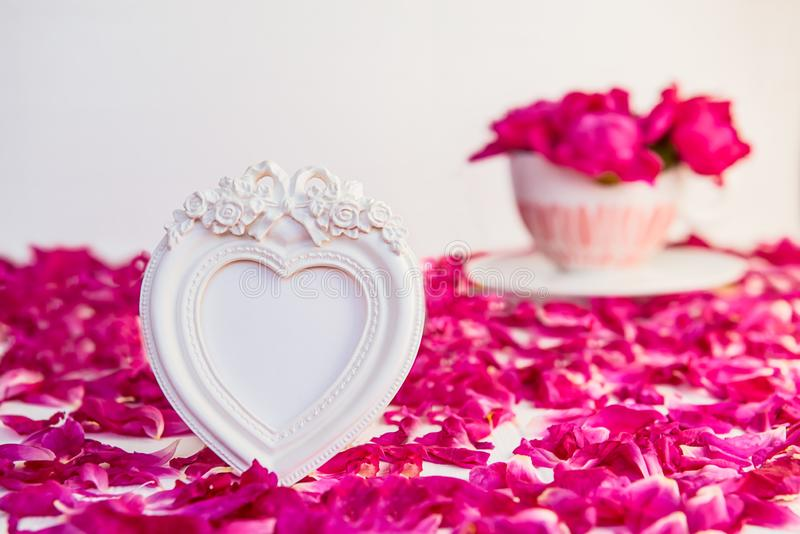 Heart shaped vintage style blank photoframe on the white table with fresh petals and bouquet of pink purple peonies in cup. Love,. Romantic, Valentines day stock images