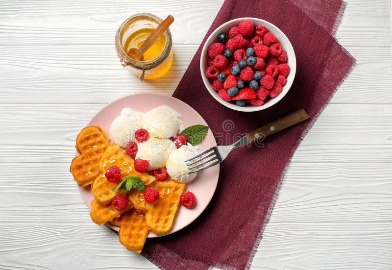 Heart shaped waffles with berries, ice cream and honey on white wooden background royalty free stock image