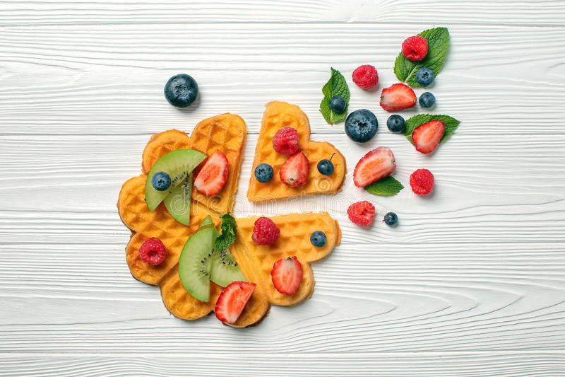 Heart shaped waffles berries and kiwi slices on white wooden background royalty free stock images