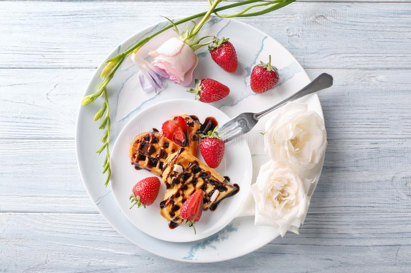 Heart shaped waffles with strawberries and chocolate sauce on plate stock images