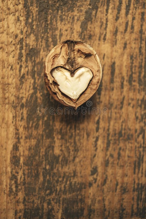 Heart-shaped walnut on a wooden background stock images