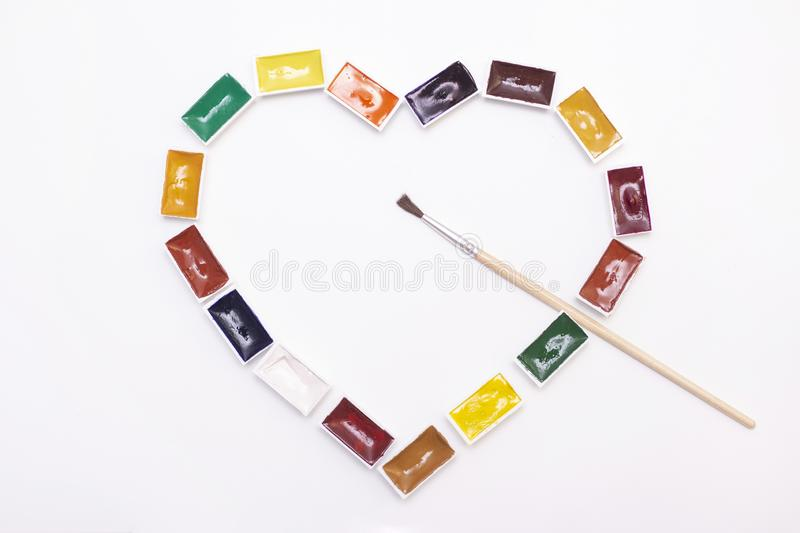 Heart shaped watercolor art paint. with brushes. palette of multi-colored paints for drawing with water. on white background. View from above. flat lay stock photo