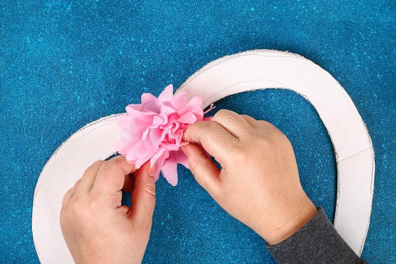 Heart shaped wreath decorated artificial flower made pink tissue paper napkins stock photo