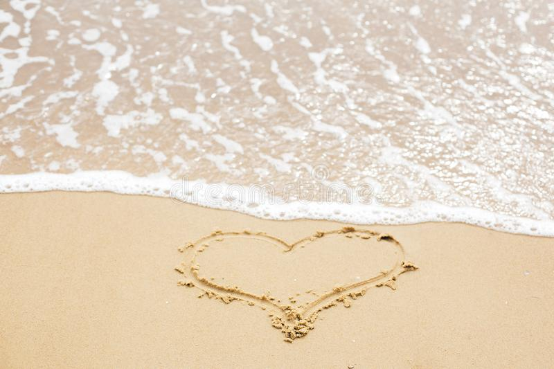 Heart sign on beach. Heart symbol on sandy beach and sea waves with foam. Love and hello summer concept. Vacation, relax and royalty free stock images