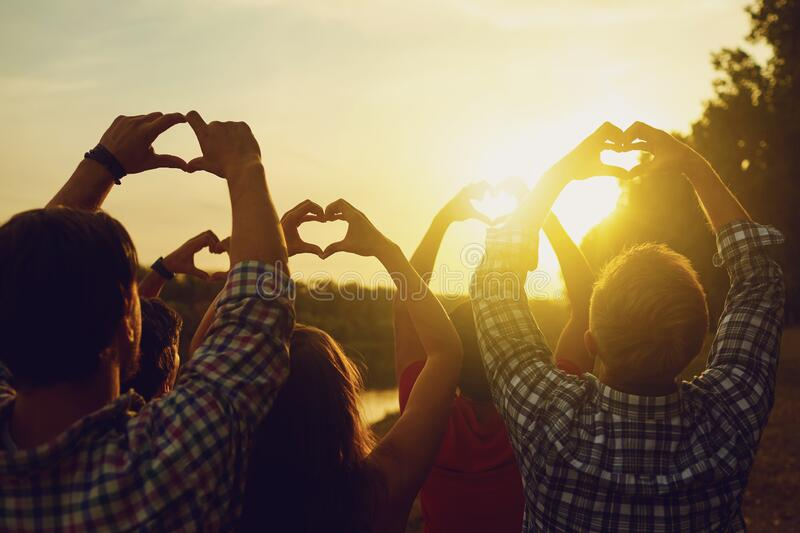 Heart sign with hands of a group of people at sunset. A group of friends raised their hands up holding a heart shape on nature in the evening in the sun royalty free stock photos