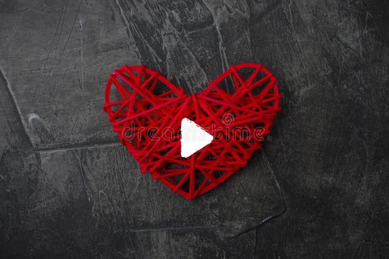 Heart with a sign Play on a dark background. Theme for Valentine`s Day. Wedding royalty free stock photo