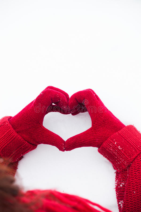 Heart sign on snow hands in red gloves stock photo