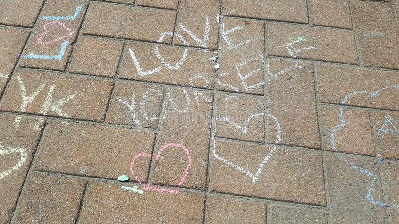 Heart sketches with the text love yourself - chalk drawing on stone pavement royalty free stock photos
