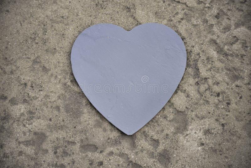 Heart slate on a stone. Heart made of graphite slate on a stone background stock image