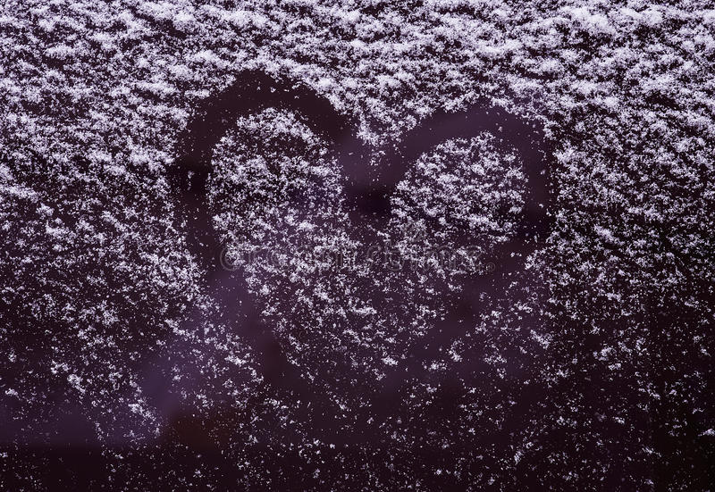 Heart on the snow-covered car windshield stock photo