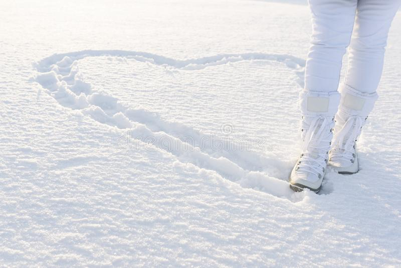Heart on snow created by footsteps. Woman walks in snow boots. Winter background. royalty free stock image