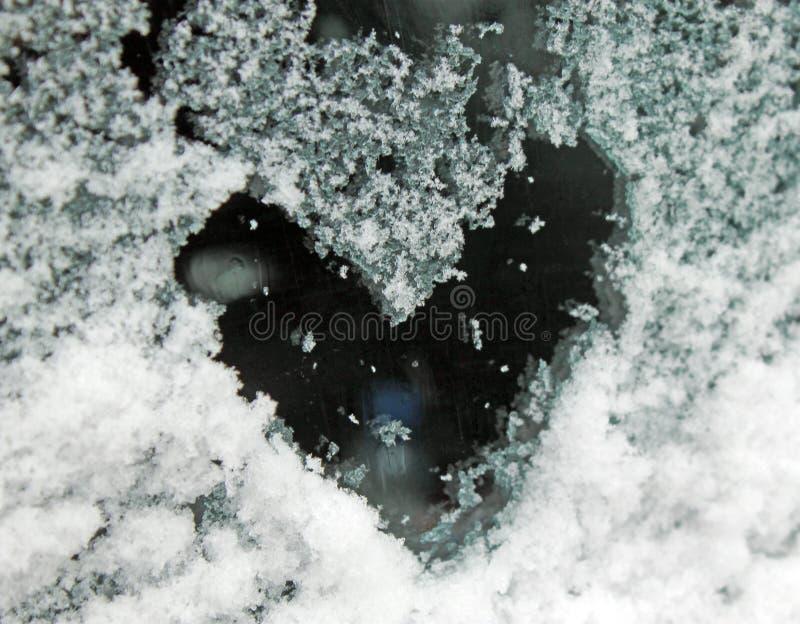 Heart of snow on the glass. sleet on glass stock photos