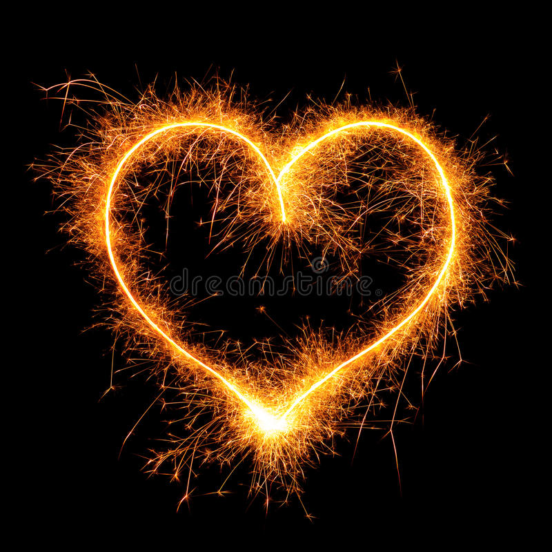 Heart from sparkler on black stock photography