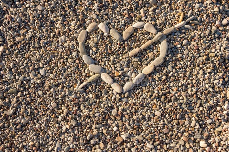 Heart of stone the Concept of unrequited love. Heart shape from white and gray pebbles. Cupid`s arrow hit the heart. Valentine`s royalty free stock image