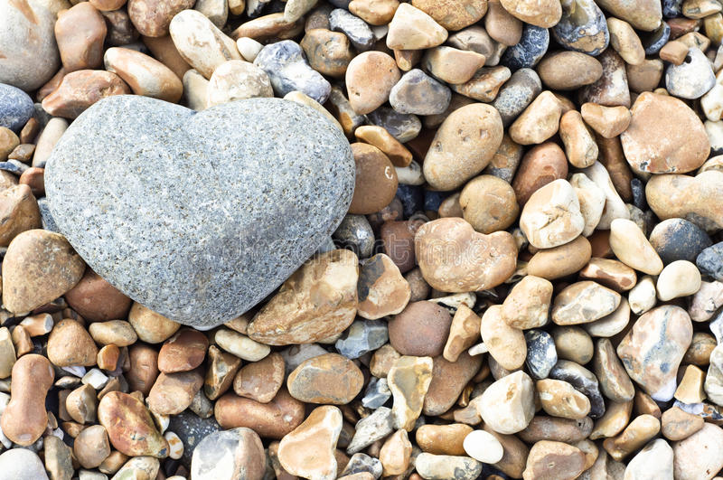 Heart Stone - Landscape Orientation. A grey heart shaped stone in upper left of frame, resting on a variety of smaller stones. Landscape (horizontal) orientation stock photo