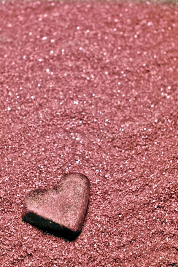Heart stone on wavy pink sand stock photo