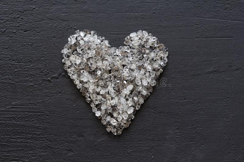 Heart of stones, love. Scattered diamonds on black background. Raw diamonds and mining, a scattering of natural diamond stones. Graphite quartz. Natural stones stock images