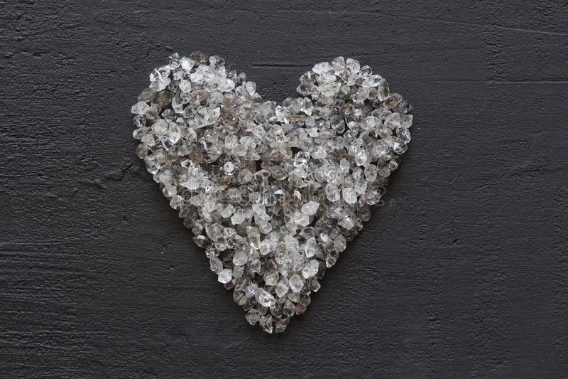 Heart of stones, love. Scattered diamonds on black background. Raw diamonds and mining, a scattering of natural diamond stones. Graphite quartz. Natural stones stock photography