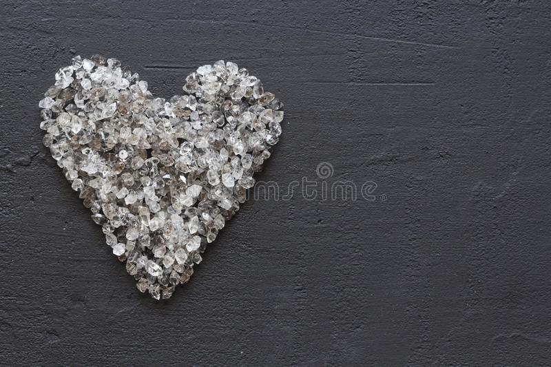 Heart of stones, love. Scattered diamonds on black background. Raw diamonds and mining, a scattering of natural diamond stones. Graphite quartz. Natural stones stock photo