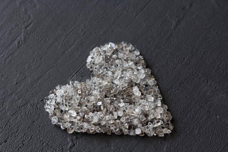 Heart of stones, love. Scattered diamonds on black background. Raw diamonds and mining, a scattering of natural diamond stones. Graphite quartz. Natural stones stock photos