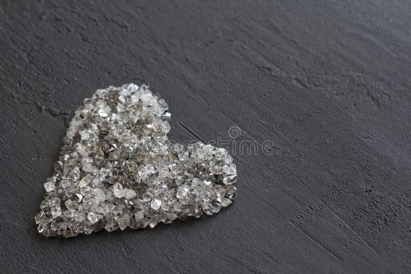 Heart of stones, love. Scattered diamonds on black background. Raw diamonds and mining, a scattering of natural diamond stones. Graphite quartz. Natural stones royalty free stock photo