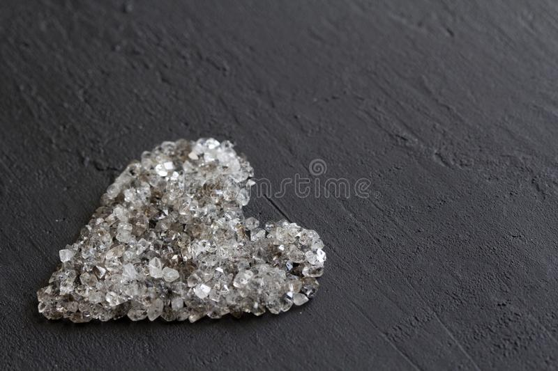 Heart of stones, love. Scattered diamonds on black background. Raw diamonds and mining, a scattering of natural diamond stones. Graphite quartz. Natural stones royalty free stock photography
