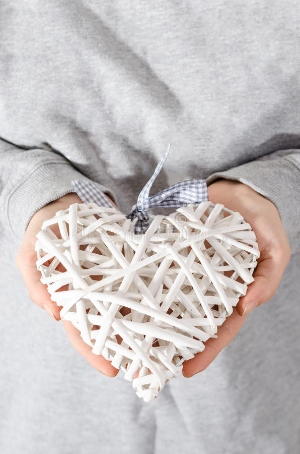 Heart of straw held in hands by women royalty free stock photo