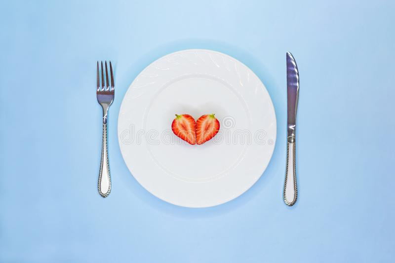 Heart of strawberry halves on white plate. Low calorie diet concept. Vegeterian raw food. Valentine Day concept stock photos
