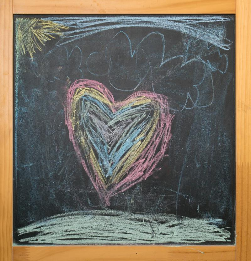Heart and sun, kids chalk drawing on black board royalty free stock images