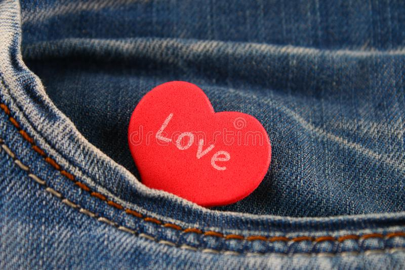 Heart - a symbol of love peeps out of the pocket of jeans trousers. The concept of the day of lovers. St. Valentine's Day. Heart - a symbol of love peeps out of royalty free stock image