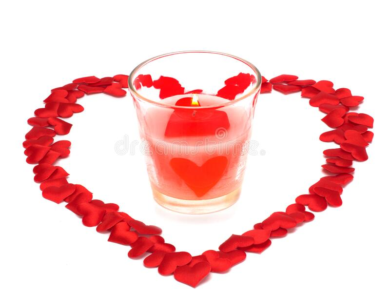 Heart, Symbol of Love and Valentine`s Day with a candle in a glass isolated on white royalty free stock images