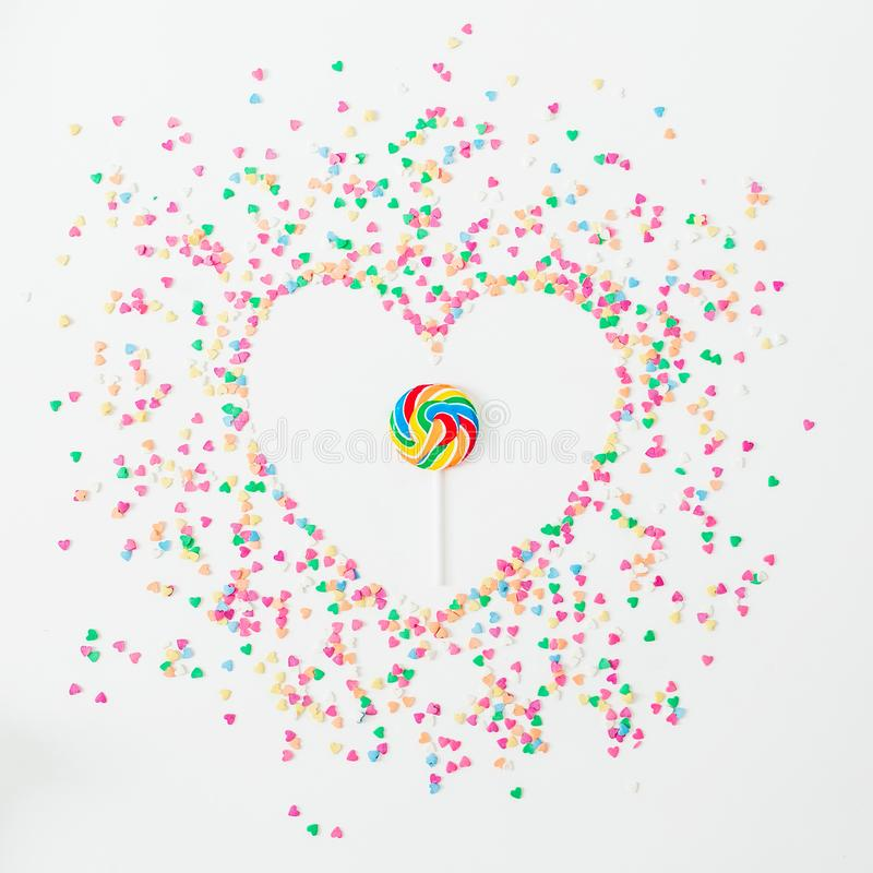 Heart symbol made of colorful bright confetti and candy on white background. Flat lay, top view copy space. Love concept stock photo