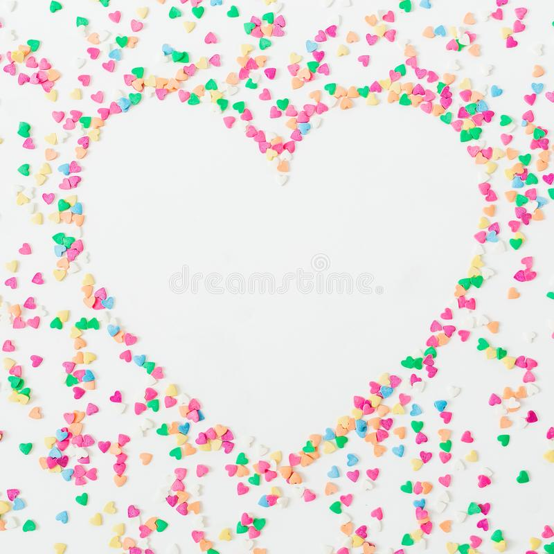 Heart symbol made of colorful bright confetti on white background. Flat lay, top view copy space. Love concept royalty free stock images