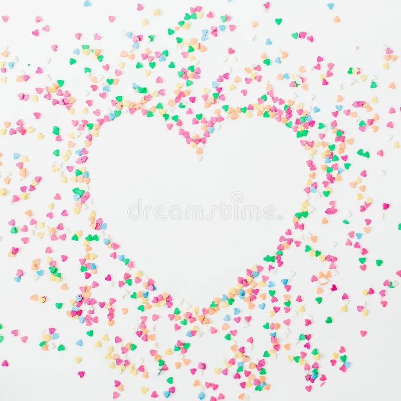 Heart symbol made of colorful bright confetti on white background. Flat lay, top view copy space. Love concept stock photography