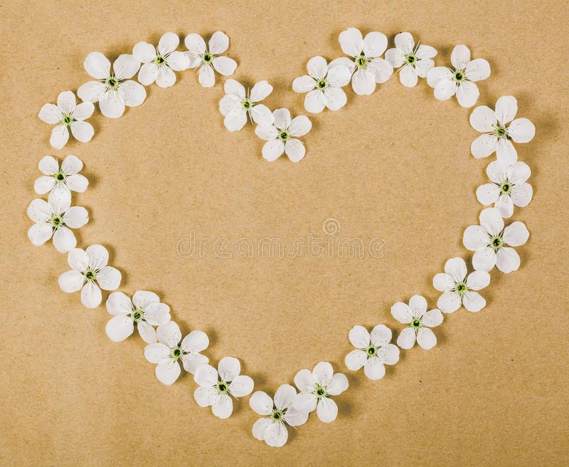 Heart symbol made of white spring flowers on brown paper background. Flat lay. stock photo