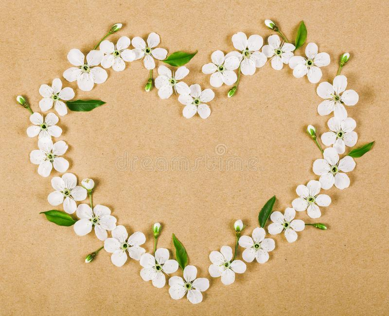 Heart symbol made of white spring flowers and green leaves on brown paper background. Flat lay. royalty free stock photos