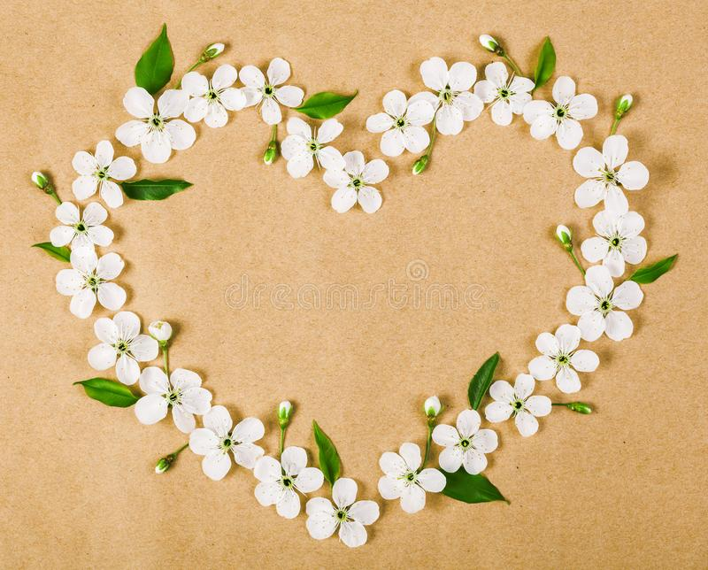Heart symbol made of white spring flowers and green leaves on brown paper background. Flat lay stock photography